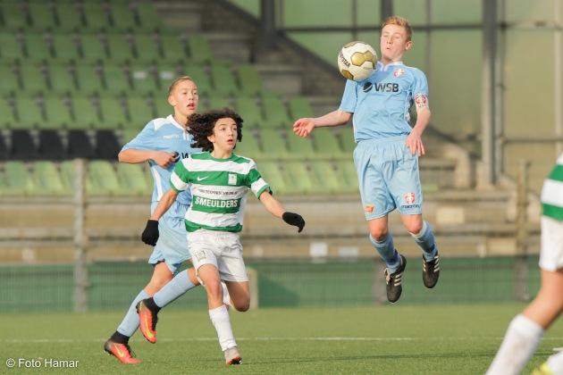 Captain van FC Dordrecht U15 onderschept tijdens jump de bal van Nuenen.