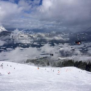 Uitzicht na eerste afdaling. Piste met sneeuw en stoeltjeslift.