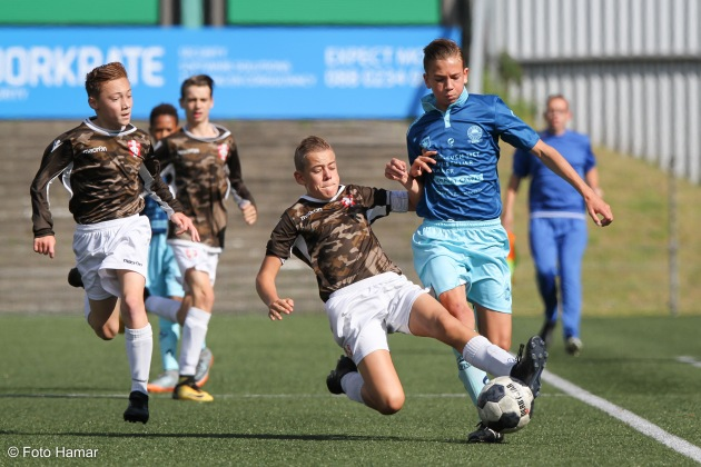 Speler van FC Dordrecht U14 maakt een sliding voor speler van Excelsior