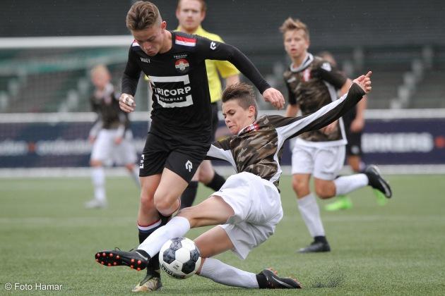 Speler van FC Dordrecht maakt sliding op de bal tegen Willem II U15