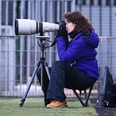 Deborah achter fototoestel met grote witte lens.